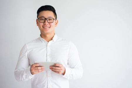 Photo for Happy Young Asian Man Holding Tablet - Royalty Free Image
