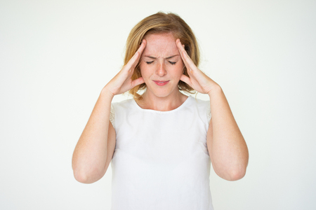 Foto de Annoyed woman suffering from terrible headache - Imagen libre de derechos