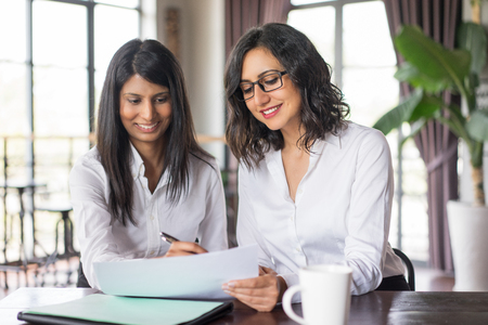 Photo for Two smiling female coworkers planning in cafe. They are sitting at table and working with document. Teamwork concept. Front view. - Royalty Free Image