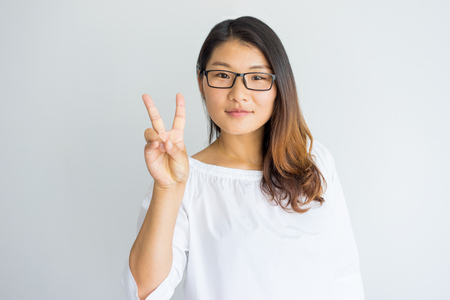 Photo for Content attractive Chinese woman in eyeglasses showing greeting gesture and looking at camera. Positive friendly girl in white blouse showing peace sign. Lifestyle concept - Royalty Free Image