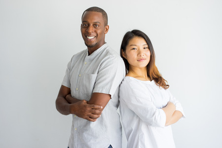 Photo for Cheerful confident young multiethnic student standing back to back and looking at camera. Positive interracial friends being leaders. Team concept - Royalty Free Image