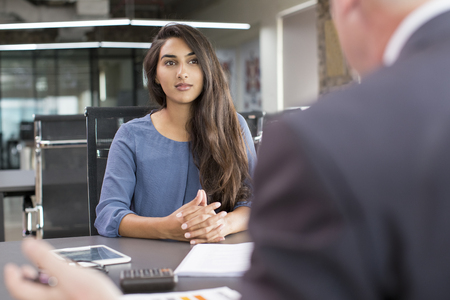 Foto de Focused Indian female customer meeting with financial advisor. Young beautiful candidate at job interview in modern office space. Business consulting or employment concept - Imagen libre de derechos