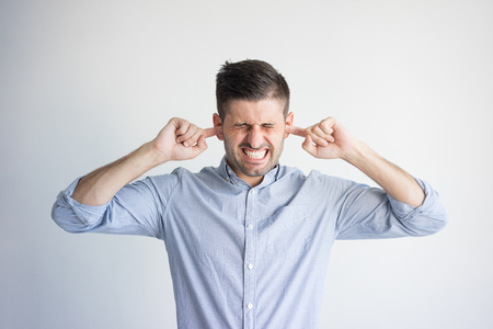 Photo for Portrait of irritated young man plugging ears with fingers. Young Caucasian man wearing blue shirt annoyed by noise. Do not want to hear concept - Royalty Free Image