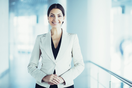 Photo pour Closeup portrait of smiling beautiful middle-aged business woman wearing jacket, looking at camera and standing in light office hall - image libre de droit