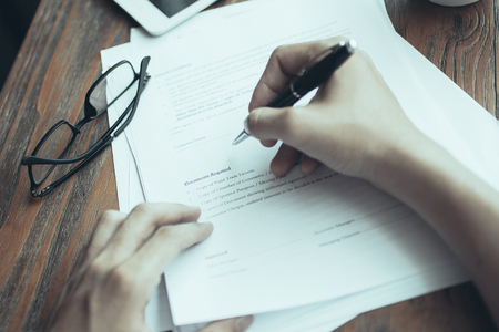Photo pour Close-up of male manager working with documents. He writing in paper. Eyeglasses, tablet, mug with coffee on table. Businessman analyzing report. Paperwork concept - image libre de droit