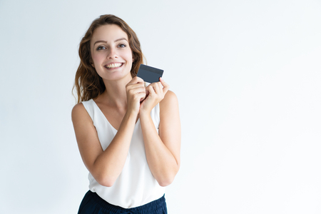 Photo pour Smiling pretty young woman holding plastic card with both hands. Lady looking at camera. Cashless payment concept. Isolated front view on white background. - image libre de droit