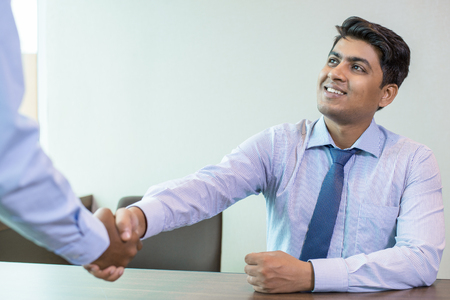 Photo for Indian businessman greeting partner in office. Business leader and his unrecognizable partner shaking hands. Business handshake concept - Royalty Free Image