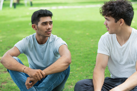 Foto de Serious Indian guy sharing problem with friend in summer park. Handsome young men sitting on grass and talking. Chatting concept - Imagen libre de derechos