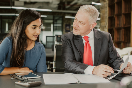 Photo for Mentor training young female professional. Middle aged grey haired man in formal suit pointing at notes and instructing young beautiful girl in casual clothes. Business coaching and mentorship concept - Royalty Free Image