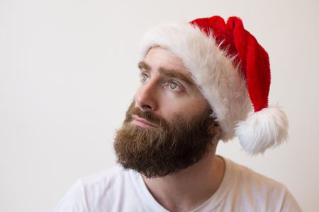 Photo for Pensive bearded man wearing Santa hat. Handsome young guy looking away. Christmas planning concept. Isolated closeup view on white background. - Royalty Free Image
