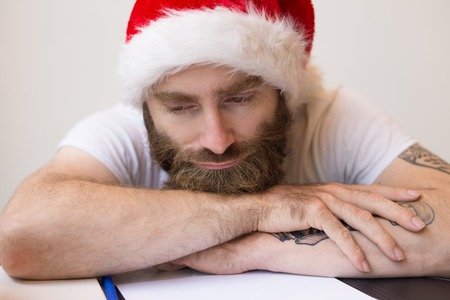 Photo for Dreamy business man wearing Santa hat and relaxing at desk. Bearded guy lying on desk with papers. Christmas and business concept. Front view. - Royalty Free Image