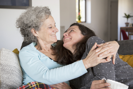 Photo pour Jolly senior mother and her daughter relaxing on sofa at home. Cheerful elderly lady and her daughter looking at each other. Family hug concept - image libre de droit