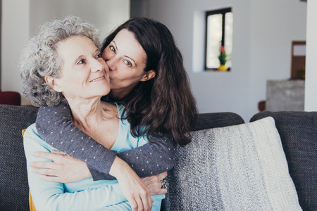 Photo pour Pretty woman kissing senior mother and hugging her from back. Smiling elderly lady spending time with young daughter. Bonding concept - image libre de droit