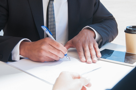 Photo for Closeup of business man writing on paper sheet at table. Business man and partner sitting at desk with tablet and coffee outdoors. Paperwork concept. Cropped view. - Royalty Free Image