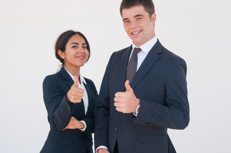 Photo for Happy confident professionals expressing approval. Young man and woman in formal suits smiling at camera and showing thumbs up. Positive feedback concept - Royalty Free Image