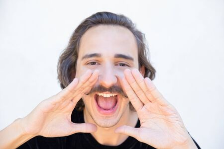 Photo for Closeup shot of man with mustache screaming. Smiling young guy looking at camera, opening mouth widely, cupping hands. Screaming concept - Royalty Free Image