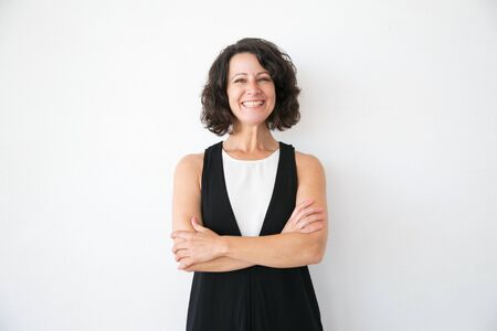 Photo pour Happy joyful woman in casual posing over white studio background. Portrait of cheerful successful middle aged business lady with arms folded smiling at camera. Female portrait concept - image libre de droit