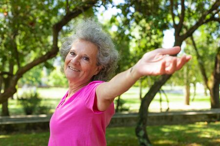 Foto de Joyful excited old lady enjoying outdoor workout. Senior grey haired woman in casual standing in park, outstretching hands and smiling at camera. Age and body training concept - Imagen libre de derechos