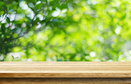 Foto de Empty wood table with blur green leaves bokeh background - Imagen libre de derechos