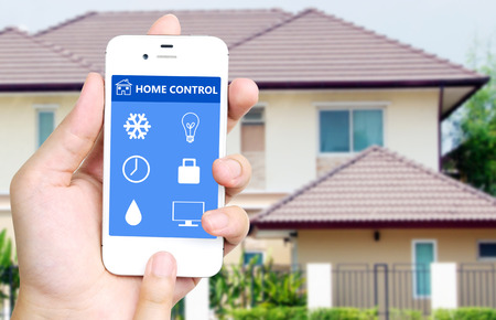 Foto de Hand holding white mobile smart phone with smart home application on the screen over blurred house background, smart home concept - Imagen libre de derechos