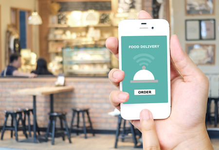 Foto de Hand holding smart phone with food delivery device on screen over blur restaurant background, food online, food delivery concept - Imagen libre de derechos