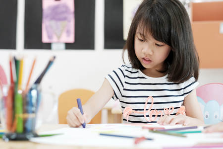 Foto de Girl drawing color pencils in kindergarten classroom, preschool and kid education concept - Imagen libre de derechos