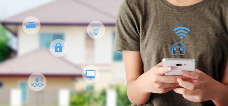 Foto de Woman using smart phone as smart home remote control mobile app over blurred house background, banner, smart home device wireless network, the internet of things concept - Imagen libre de derechos
