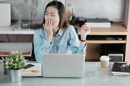 Photo pour Young asian businesswoman yawning while working with laptop computer at office, woman in casual office lifestyle concept - image libre de droit