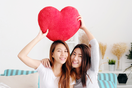 Foto de Young cute asia lesbians holding red heart shape willow together smiling with happiness at home, LGBT, couple lesbians, valentine's day concept - Imagen libre de derechos