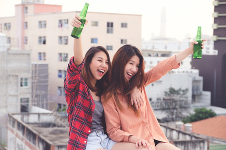 Photo for Two asian women drinking at rooftop party, outdoors celebration, LGBT couple - Royalty Free Image