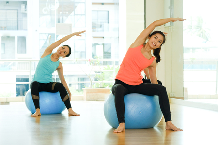 Photo pour Young asian women practicing yoga ball, fitness stretching flexibility pose, working out, healthy lifestyle, wellness, well being - image libre de droit