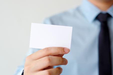 Foto de Businessman hand holding blank white business card with copy space for text, business mock up background concept - Imagen libre de derechos