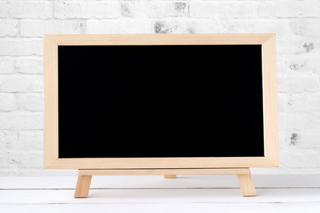 Foto de Blank chalkboard standing on white table over white brick wall background, space for text - Imagen libre de derechos