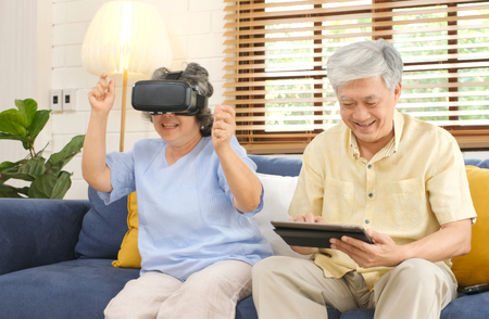 Foto de Senior asian couple playing virtual reality headset and using digital tablet in home living room with happiness emotion, retirement lifestyle and technology - Imagen libre de derechos