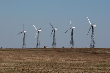 Foto de Rotatingpower saving windmills built on dried field in rural environment. - Imagen libre de derechos