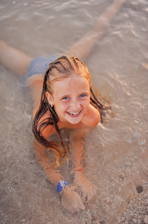 Photo for happy kid with long plaits having fun on the beach - Royalty Free Image