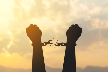 Foto de silhouette hand with chain is absent and blurred sky in sunrise background - Imagen libre de derechos