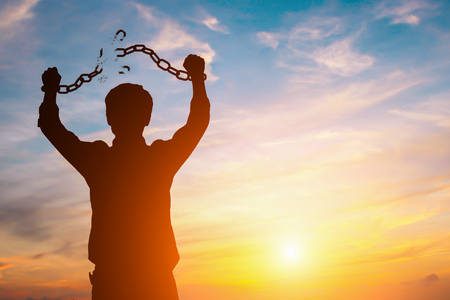 Foto per Silhouette image of a businessman with broken chains in sunset - Immagine Royalty Free