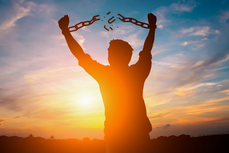 Foto de Silhouette image of a businessman with broken chains in sunset - Imagen libre de derechos