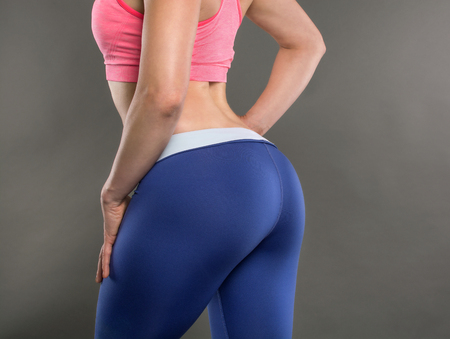 Photo pour Closeup of fitness woman with fit cheeks, tight hips and firm buttocks in workout leggins. Perfect female ass in shape of sexy bottom and big butt. Slim girl body isolated on white background. - image libre de droit