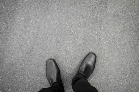 Photo pour black shoes standing on the asphalt concrete floor - image libre de droit