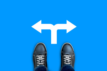 Photo pour Black casual shoes standing on blue floor at the crossroad making decision which way to go. Left or right.  - image libre de droit