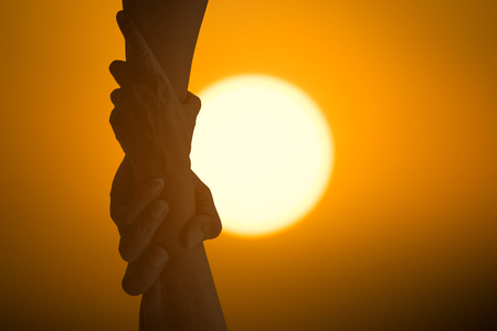 Foto de Silhouette help hands holding together under the sun representing friendship, partnership, help and hope, donation, assistance. - Imagen libre de derechos