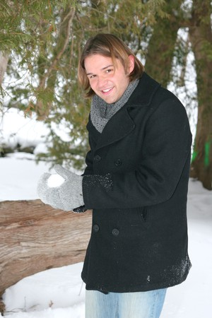 one young twenties man making a snowball during winter