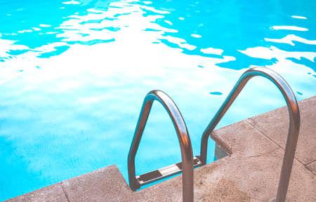 Foto de Metal stairs of a salt water pool on a summer day. - Imagen libre de derechos