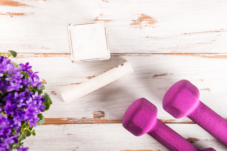 Ladies Sports Accessories such as purple dumbbells with blank wooden block for date and purple flowers nearby. Fitness, sport and healthy lifestyle concept. Top view, copy space