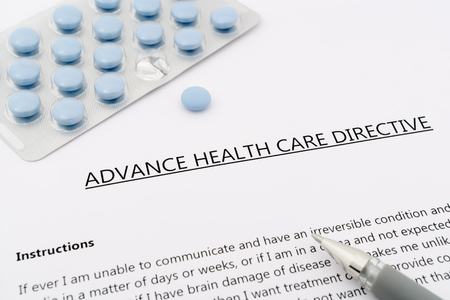 Foto per advance health care directive with blue pills to the gray pen - Immagine Royalty Free