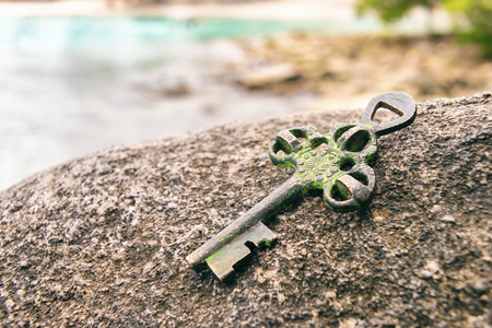 Photo for Treasure key lost on rock at the beach. Opportunity or Mystery concept. - Royalty Free Image