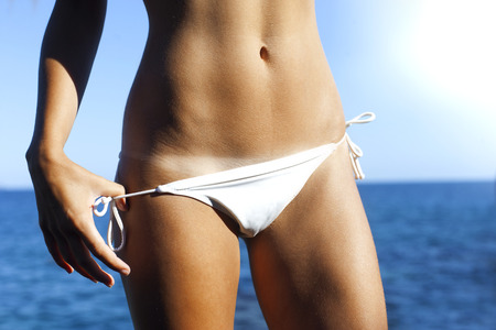 Woman bronze tanned body in summer with bikini line