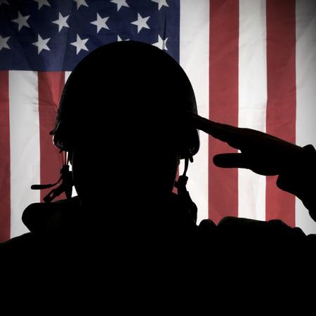 Foto de American USA soldier saluting to USA flag - Imagen libre de derechos